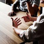 Lähikuva pöydän ääressä keskustelevien ihmisten käsistä.