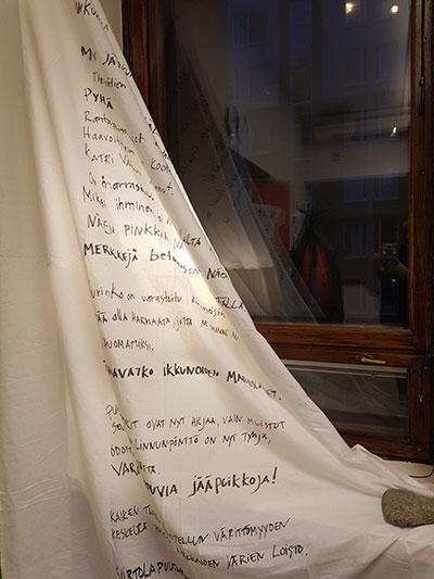 Sivulla oleva runo on kirjoitettu lakanaan, joka on asetettu osittain ikkunan eteen verhon tavoin.