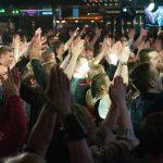 Suuri joukko iloisia ihmisiä kädet ylhäälle nostettuna.